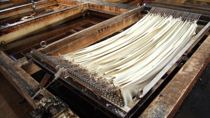 革のなめし剤であるタンニンの水槽に革を浸す