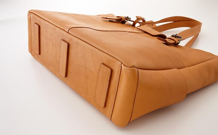 バッグの底はクッション材。安定感と床を傷つけないように鋲の代わりに革のパッチをあてる