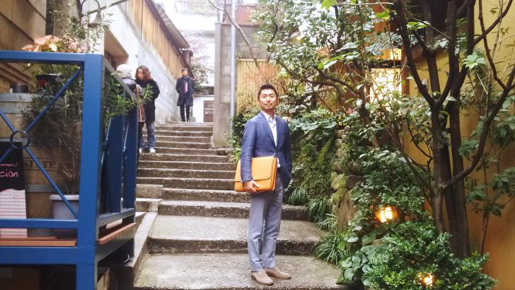 神楽坂でmoeの革のクラッチバッグを持つ大滝さん