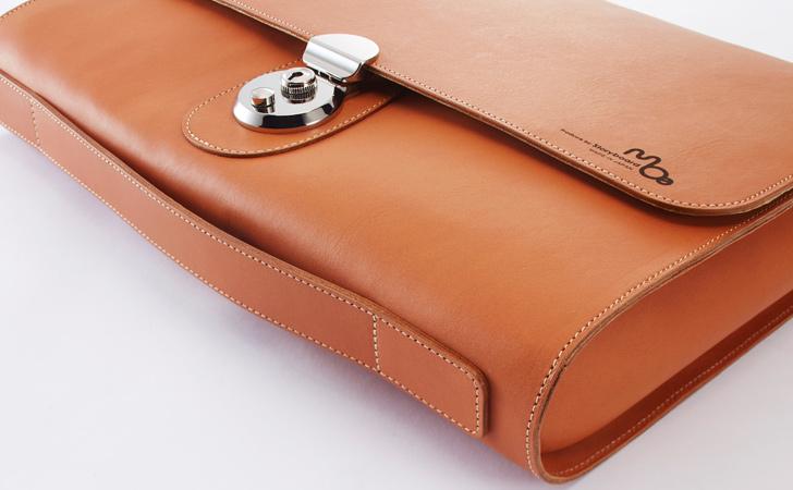 わん曲した底面に持ち手を固定するベルトの付いた革のクラッチバッグ